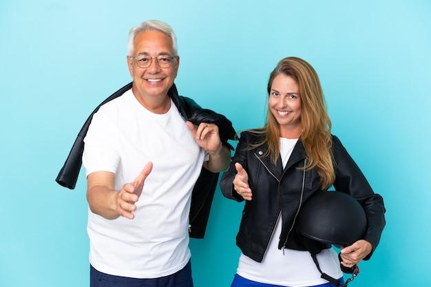Couple de motards d'âge moyen avec un casque de moto isolé sur fond bleu se serrant la main pour conclure une bonne affaire