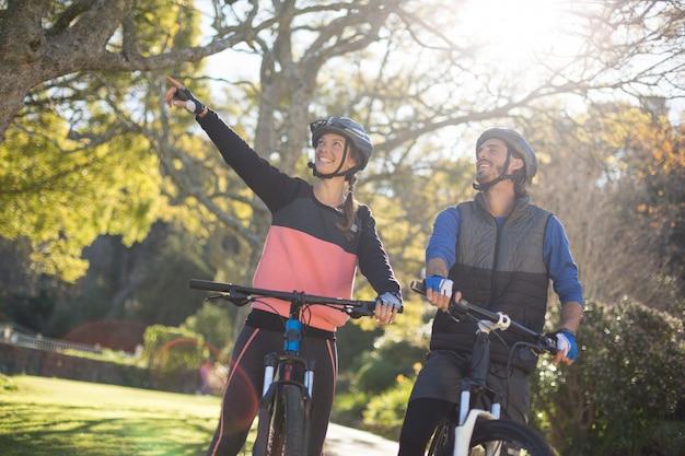 Couple de motards avec vélo de montagne pointant à distance