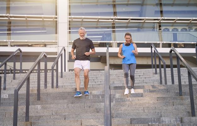 Couple motivé homme et femme d'âge moyen en tenue de sport montant un escalier tout en