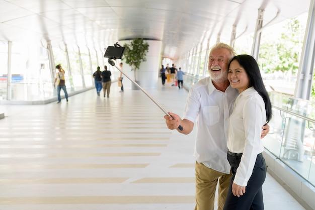 Couple multiethnique mature heureux et amoureux tout en explorant la ville de bangkok