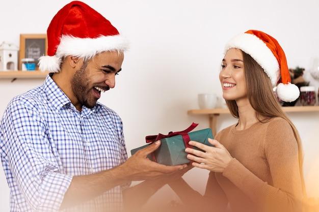 Couple multiethnique romantique en chapeaux de noël échangeant des cadeaux