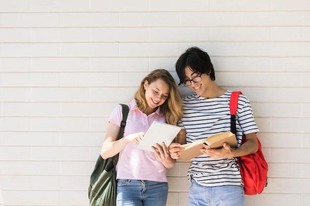 Couple multiracial à l'aide d'une tablette et d'un livre de lecture contre un mur blanc