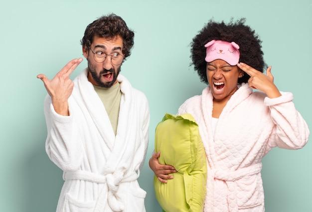 Couple multiracial d'amis à l'air malheureux et stressé, geste de suicide faisant un signe d'arme à feu avec la main