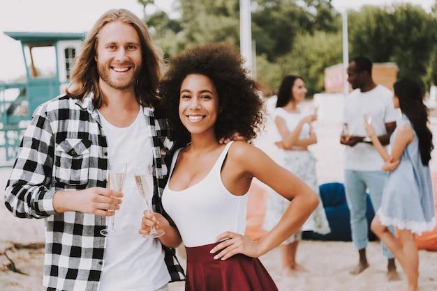 Couple multiracial buvant du champagne sur la plage
