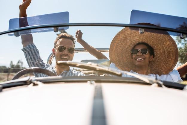 Couple multiracial dans une voiture d'époque convertible