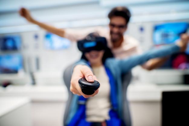 Couple multiracial s'amusant avec des lunettes de réalité virtuelle alors qu'une fille assise sur une chaise dans le magasin de technologie. service client. temps de magasinage.