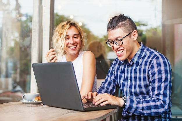 Couple multiracial utilisant un ordinateur portable et riant