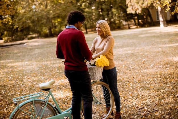 Couple multiracial avec vélo debout dans le parc en automne