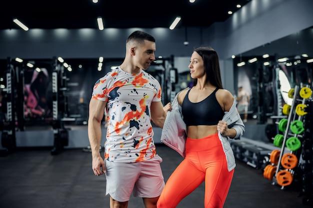 Couple musclé debout dans la salle de gym et posant. fitness intérieur, relation, vie saine