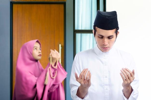 Couple musulman asiatique debout tout en levant les mains et priant ensemble à la maison