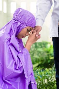 Couple musulman asiatique, homme et femme, priant à la maison