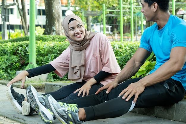 Couple musulman s'asseoir et se détendre pendant leur pause d'exercice dans le jardin