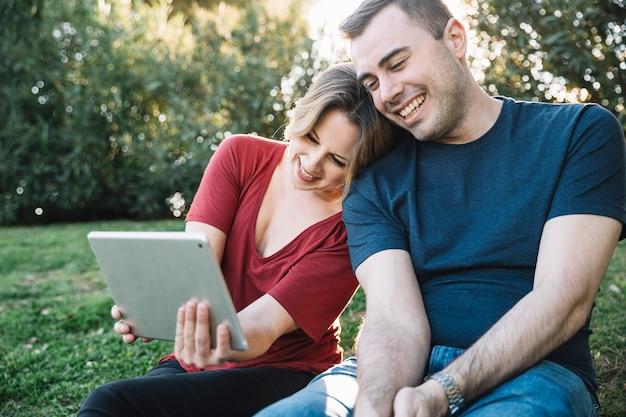 Couple, navigation tablette sur le parc