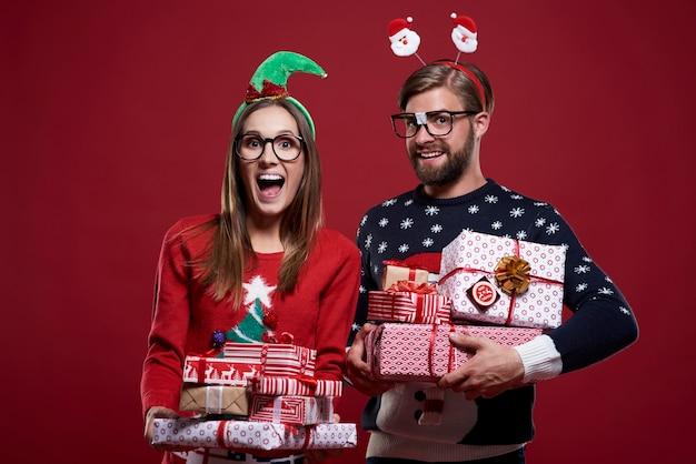 Couple de noël transportant de lourds cadeaux