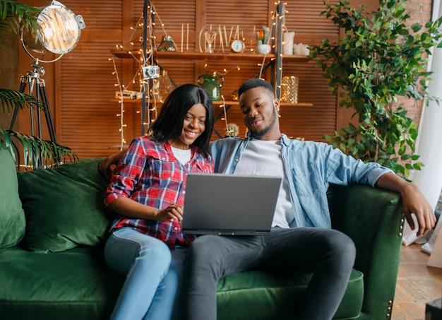 Couple noir assis sur un canapé et à la recherche d'un ordinateur portable à la maison.