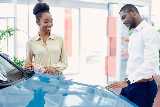 Couple noir en contemplation avant de faire l'achat dans la salle d'exposition de voitures