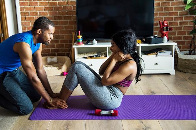 Couple noir exerce à la maison ensemble