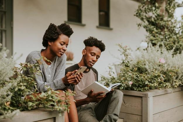Couple noir lisant un livre et jouant au téléphone