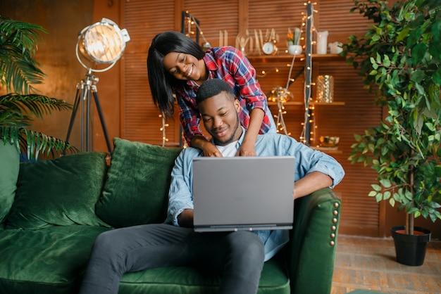 Couple noir avec ordinateur portable s'amusant sur le canapé