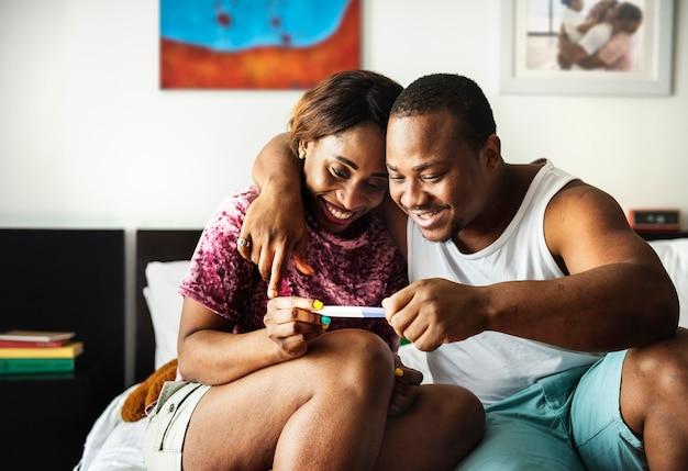Couple noir regardant test de grossesse