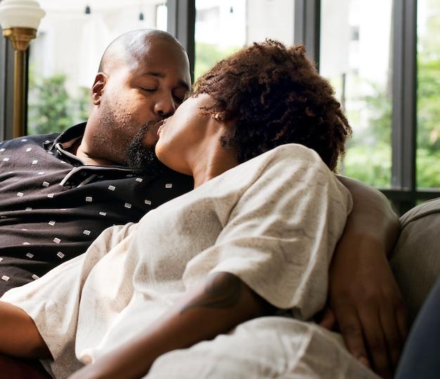 Couple noir s'embrasser sur le canapé