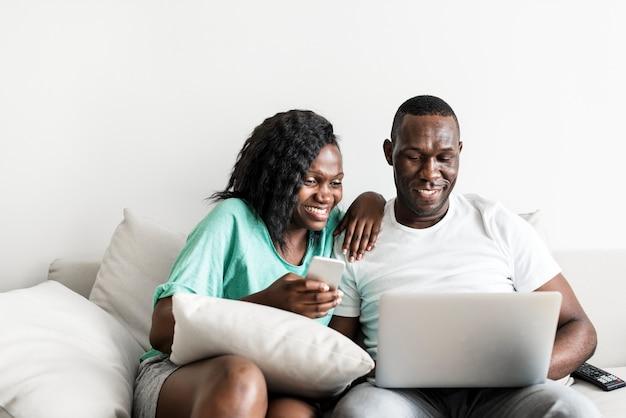 Couple noir utilisant des appareils numériques