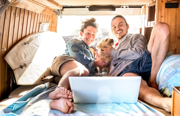 Couple de nomades numériques avec un chien mignon utilisant un ordinateur portable sur un mini-van rétro - concept d'inspiration de vie de voyage avec des personnes indépendantes lors d'un voyage d'aventure en mini-fourgonnette en regardant un ordinateur lors d'un moment de détente - filtre chaud