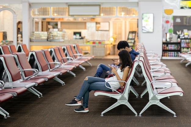 Couple non identifié utilisant son téléphone portable assis sur une chaise dans la zone lounge.