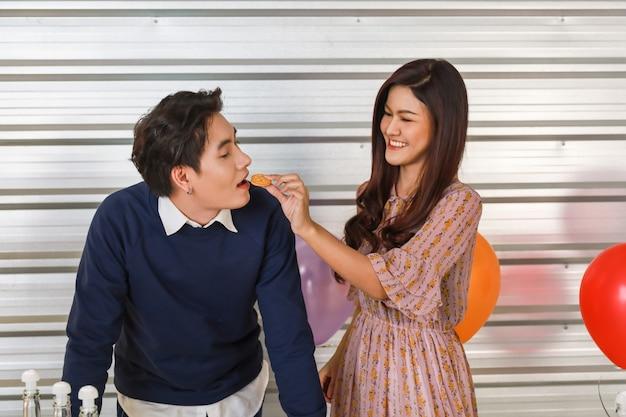 Couple, nouvel an, valentin et concept d'assaisonnement de vacances. portrait d'un bel homme asiatique et d'une femme souriante tenant un cookie et le mettre à la bouche de l'homme avec un ballon de fête coloré.