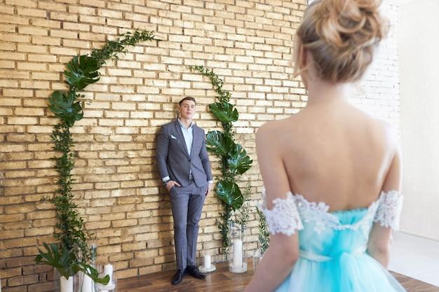 Couple nouvellement marié, couple amoureux avant le mariage. homme et femme s'aimant. la mariée en robe turquoise et le marié en costume bleu. décor de mariage, zone de photo de mariage