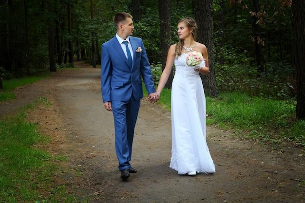 Un couple nouvellement marié marche sur les sentiers du parc se tenant la main et se regardant.
