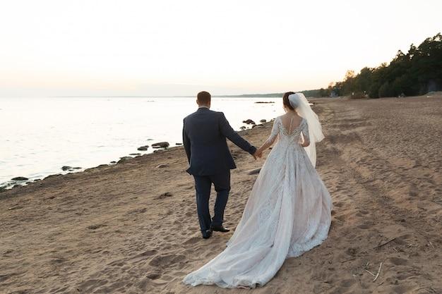Couple nouvellement marié s'éloignant ensemble sur la plage