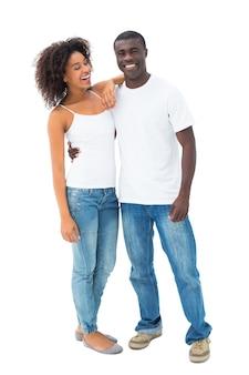 Couple occasionnel en jeans et tops blancs posant