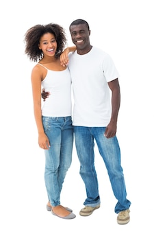 Couple occasionnel en jeans et tops blancs, souriant à la caméra