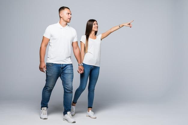 Couple occasionnel marche vers la caméra en se regardant isolé sur un mur blanc