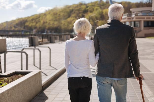 Couple ordinaire amical d'âge moyen se reposant ensemble tout en longeant la route et en profitant du temps
