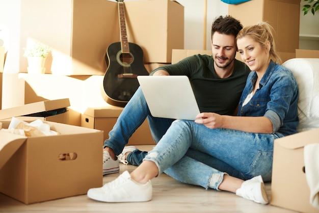 Couple avec ordinateur portable autour de boîtes en carton