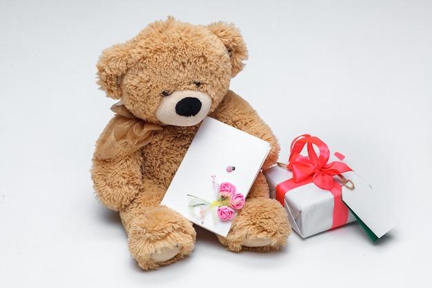 Couple d'ours en peluche avec coeur rouge et cadeau sur fond blanc. concept de la saint-valentin.