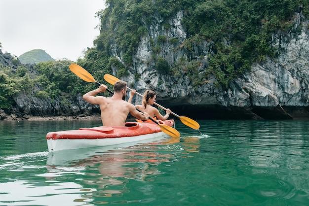 Couple paddle sur kayak dans la baie d'halong. vue depuis l'arrière sur la grotte calcaire avec de l'eau azur de ha long, viet nam.