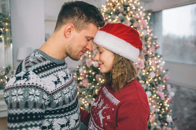 Couple paisible et attrayant gardant les yeux fermés et se touchant le front. ils se tiennent devant l'arbre de noël dans une salle décorée.