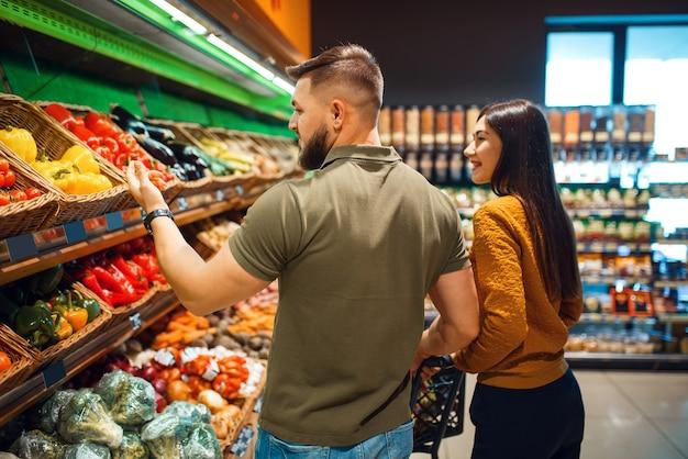 Couple avec panier en supermarché épicerie ensemble