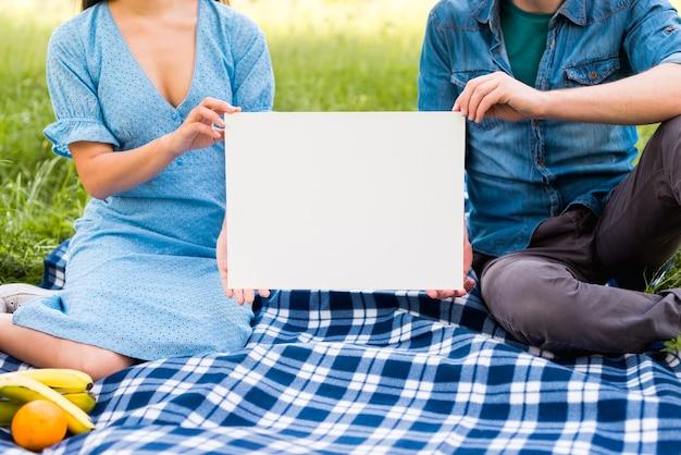 Couple avec papier blanc assis sur une couverture