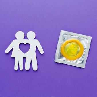 Couple de papier à côté du préservatif jaune