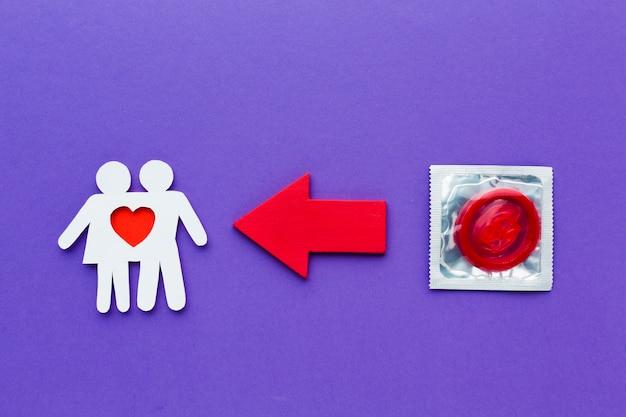 Couple de papier à côté du préservatif rouge