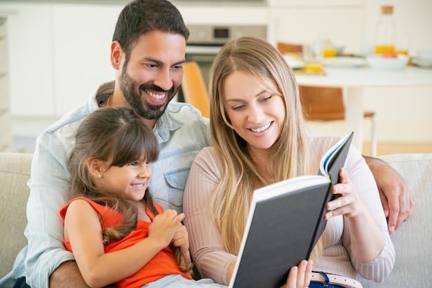 Couple de parents joyeux et petite fille aux cheveux noirs assis sur un canapé dans le salon, lisant un livre ensemble et riant.