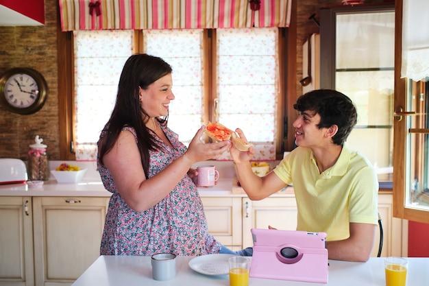 Un couple de parents prend son petit-déjeuner dans la cuisine