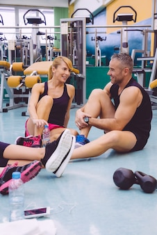 Couple parlant avec des amis assis sur le sol d'un centre de remise en forme après une dure journée d'entraînement