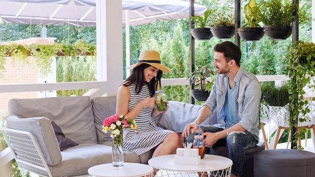 Un couple parle, boit des cocktails et passe du bon temps ensemble assis dans un café.