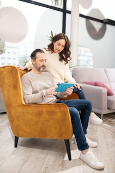 Couple passant leur temps dans le salon de meubles à la recherche de modèles en ligne