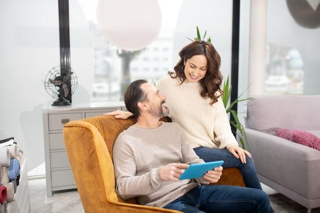 Couple passant leur temps dans le salon de meubles à regarder une vidéo